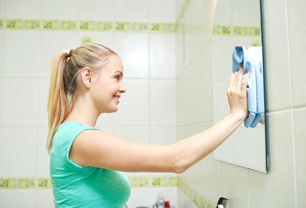 Девушка чистит зеркало в ванной