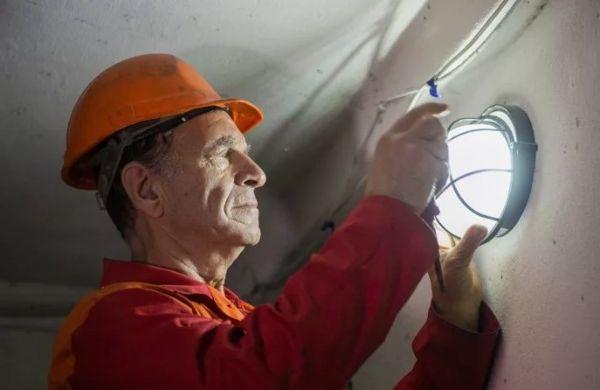 Электрик меняет лампочку