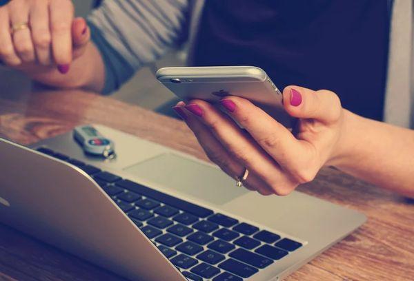 Девушка с телефоном за компьютером